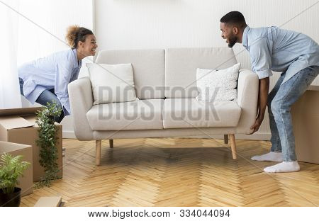 Moving Concept. Cheerful Afro Spouses Placing Couch Furnishing Empty Room In New House After Relocat
