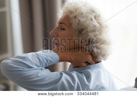 Tired Senior Grandma Rubbing Stiff Neck Suffering From Fibromyalgia Pain