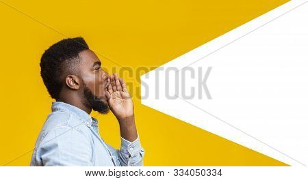 African American Man Making Loud Announcement At Copy Space, Holding Hand Near His Open Mouth Over Y