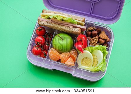 Lilac Lunch Box With Useful Food For Lunch And Snack: Sandwich, Vegetables, Fruits, Nuts And Eggs On