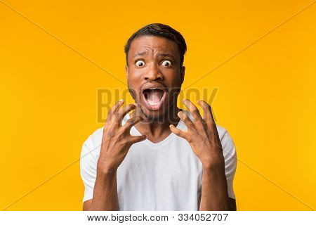 Fright. Terrified Afro Man Shouting Holding Hands Near Face Looking At Camera Standing Over Yellow B