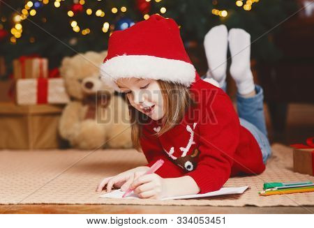 Dreamy Little Girl In Red Xmas Hat Writing Letter To Santa Under Xmas Tree, Making Wishes On Christm