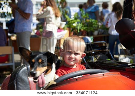 Ukraine, Shostka - September 3, 2019: A Boy With A Dog Is Sitting In A Sidecar Of A Red Retro Motorc
