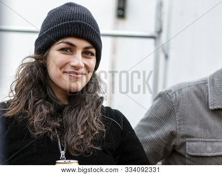 Beautiful Woman Smiling Outside Drinking Beer, Having Fun With Friends