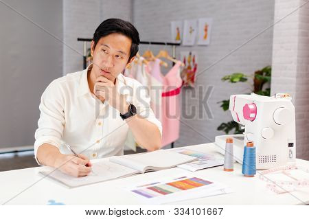 Calm Adult Asian Self Employed Tailor Looking Away And Pondering While Sitting At Table With Sewing