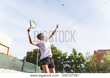 Young Man Playing Tennis Outdoors.