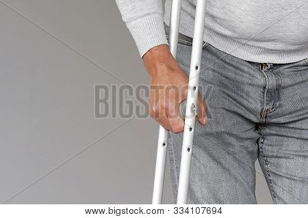 Man on crutches on a gray background. Close-up a elderly man walking with crutches. poster