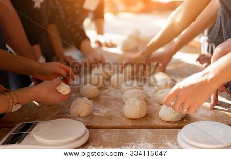 Close-up Hands Forming Dough Balls For Baking Buns On A Wooden Table During Manufacture. Culinary Ma