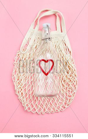 Reusable Bottle On Pink Background. Glass Bottle And Mesh Bag. Vertical Photo
