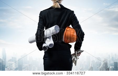 Woman Architect Standing With Technical Blueprints And Safety Helmet In Hands. Back View Of Engineer