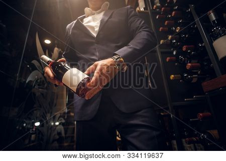 Expirienced Wine Sommelier Is Choosing Good Wine For Tasting At Private Wine Cellar.