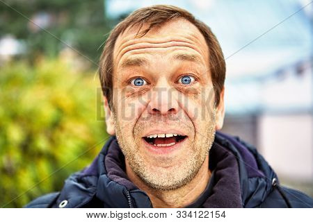 The Surprised Face Of A Man Of Fifty Years Old Against The Background Of A European Street, Close-up