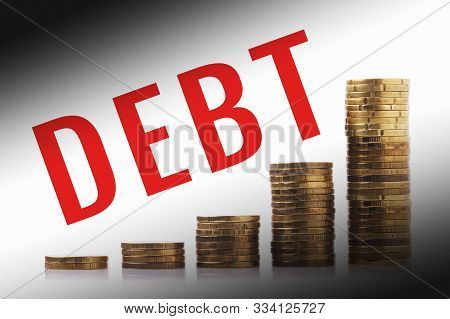 Growing Debt. Piles Of Coins And The Inscription Duty.  Increasing Credit Indebtedness