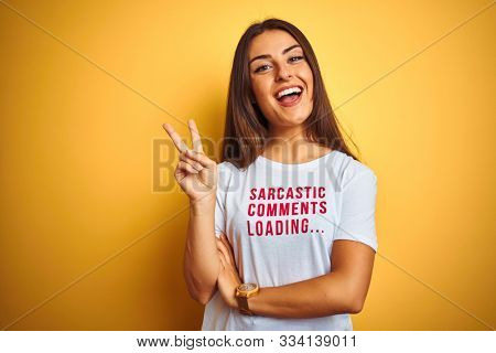 Beautiful woman wearing fanny t-shirt with irony comments over isolated yellow background smiling with happy face winking at the camera doing victory sign. Number two.