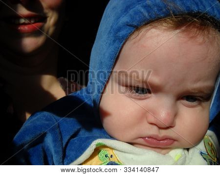 Mother Holds In Her Arms A Young Child 6 Months Old. The Baby Has A Puzzled Face. Mom Smiles. The Ch