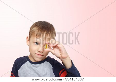 Little Boy Takes Fish Oil. Vitamins. The Child Holding Omega-3 Capsule Between His Fingers. Polyunsa