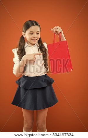 Purchase You Need To See. Cute Little Girl Pointing Finger At Purchase On Orange Background. Adorabl