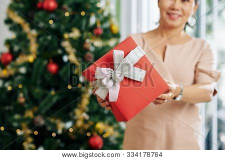 Smiling Aged Woman Giving Red Chirstmas Present With Silver Bow, Selective Focus