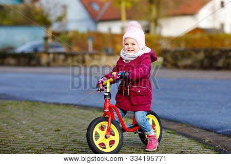 Cute Little Toddler Girl Riding On Run Balance Bike To Daycare, Playschool Or Kindergarden. Happy He