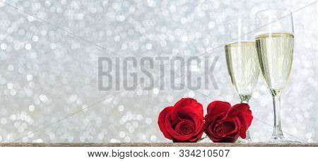 Champagne and red roses on wooden table over holiday silver glitter festive background