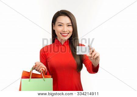 Asian Vietnamese Woman In Ao Dai Traditional Red Dress Holding Blank Credit For Shopping In Lunar Ne