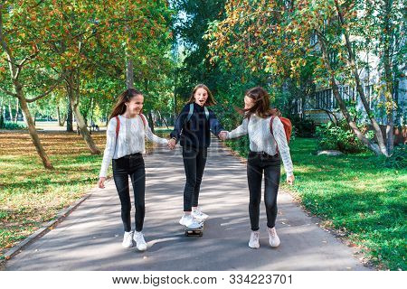 Girls Teenage Schoolgirls Ride A Skateboard After School, Happy Smiling, Emotions Of Joy, Delight An