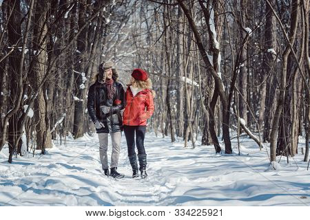 Woman and man enjoying winter in the snow having a walk in the forest