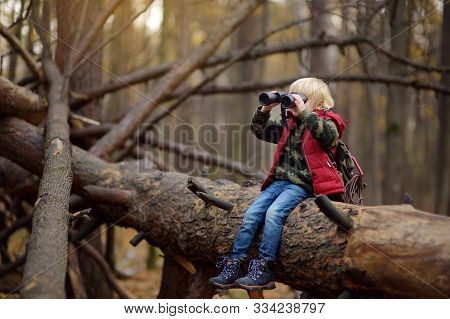 Little Boy Scout With Binoculars During Hiking In Autumn Forest. Child Is Sitting On Large Fallen Tr