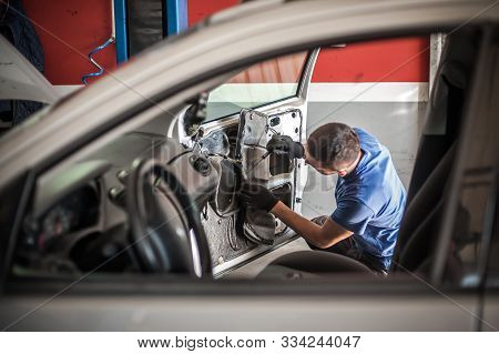 Car Mechanic Works On The Interior Of A Car Door