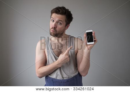 Happy Unkempt And Untidy Young Man Showing Blank Screen Of His Mobile Phone Smartphone.
