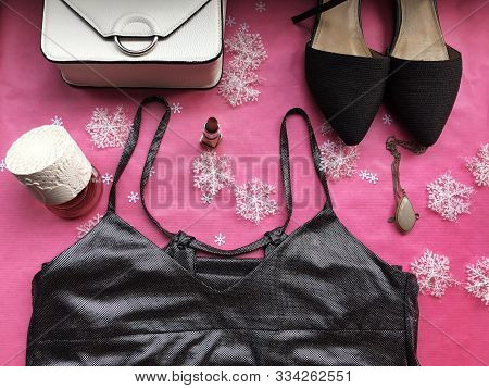 Black Female Shoes, White Handbag, Silver Dress, Perfume, Lipstick And Necklace On Pink Background W