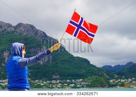 Female Tourist With Norwegian Flag Enjoying Fjord Lysefjord View. National Route Ryfylke. Vacation A