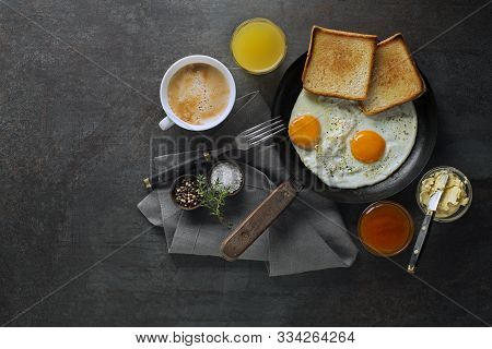 Breakfast Served With Pan Of Fried Eggs, Jam, Butter, Coffee And Juice On The Table Top View. Health