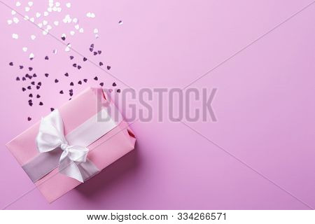 valentines day celebration, greeting card mockup, surprise for beloved. festive background with gift box and festive heart shaped sparkles on pink table, free space for text design poster