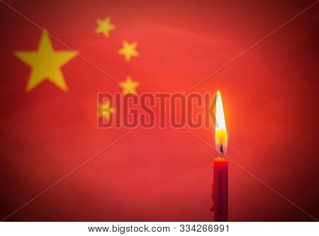 Burning Candle On The Background Of The Flag Of China. The Concept Of Mourning And Sorrow In The Cou