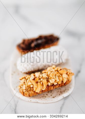 Set Of Three Homemade Eclairs On Marble Background. Close Up View Of Delicious Healthy Profitroles W