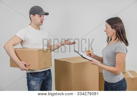 Delivery guy transported all the cardboard boxes into new flat. Young woman found some discrepancies in the consignment and doesnt want to put a signature. poster