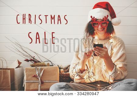 Christmas Sale Text Sign On Stylish Happy Girl In Santa Hat Looking At Phone Screen In Festive Chris