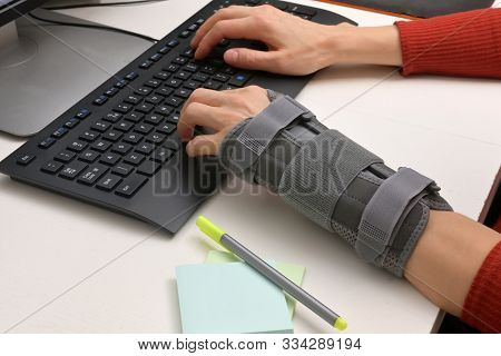 Contused Woman Hand In Stabilizer Working On Computer