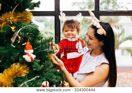 Young Beautiful And Happy Asian Mixed With Caucasian Mother And Daughter Smiling Inside Home With Ch