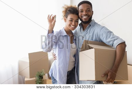 Own House. Happy Black Couple Showing Key Holding Moving Box And Hugging Standing In New Home.