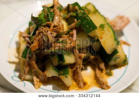 Spicy Pulled Pork And Cucumber Cold Appetiser On A White Plate