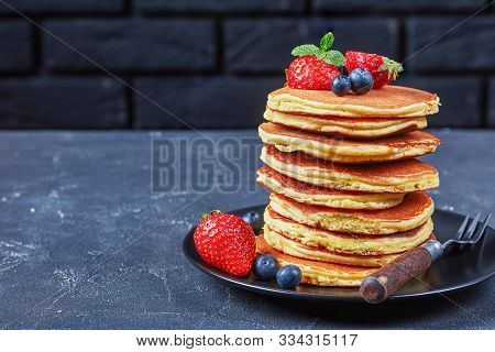 Stack Of Almond Flour Pancakes On A Black Plate With Strawberries, Blueberries And Mint On A Concret