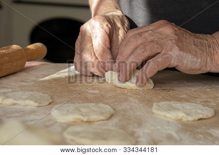 The Old Womans Overworked Hands Are Making Pies Out Of Dough. Hand-made Homework With Baked Goods