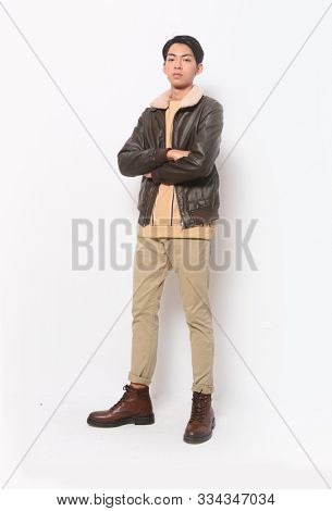 Full length portrait of s young male person standing in black leather jacket with khaki pants and brown leather boots posing