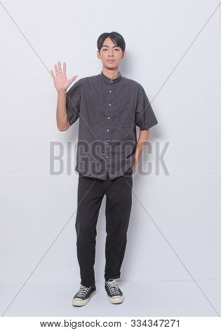 full length young man in wearing black short sleeve shirt with black jeans doing stop sing with palm of the hand.