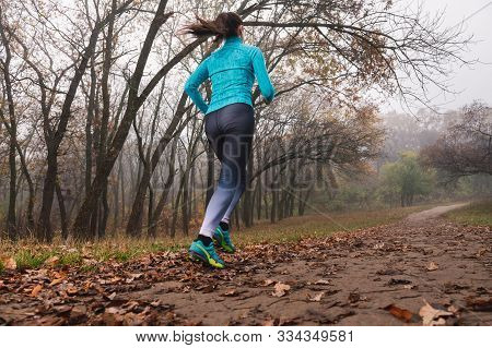 Young Female Jogging In Blue Sportswear Outdoors Back View. Fallen Foliage On The Ground, Autumn Fog