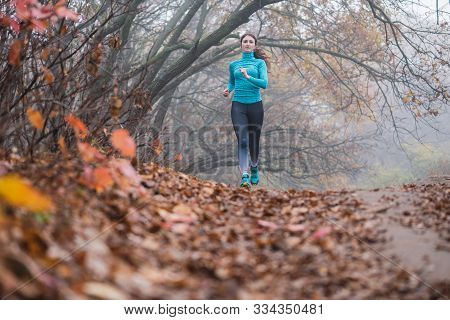 Front View Of Attractive Healthy Fit Young Sporty Woman Jogging Towards Camera In Misty Forest In Au