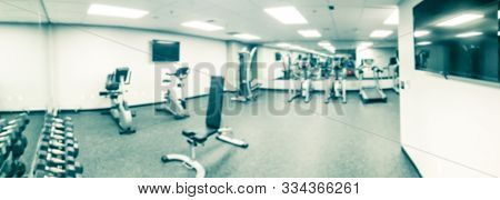 Panoramic blurry background treadmill, elliptical and workout equipments at fitness center in USA poster
