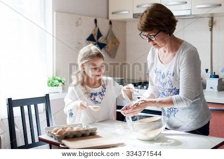 Family Is Cooking In Cozy Kitchen At Home. Mother And Child Are Making Food And Meal. Woman And Litt